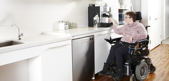 Person using a wheelchair getting coffee from the coffee machine
