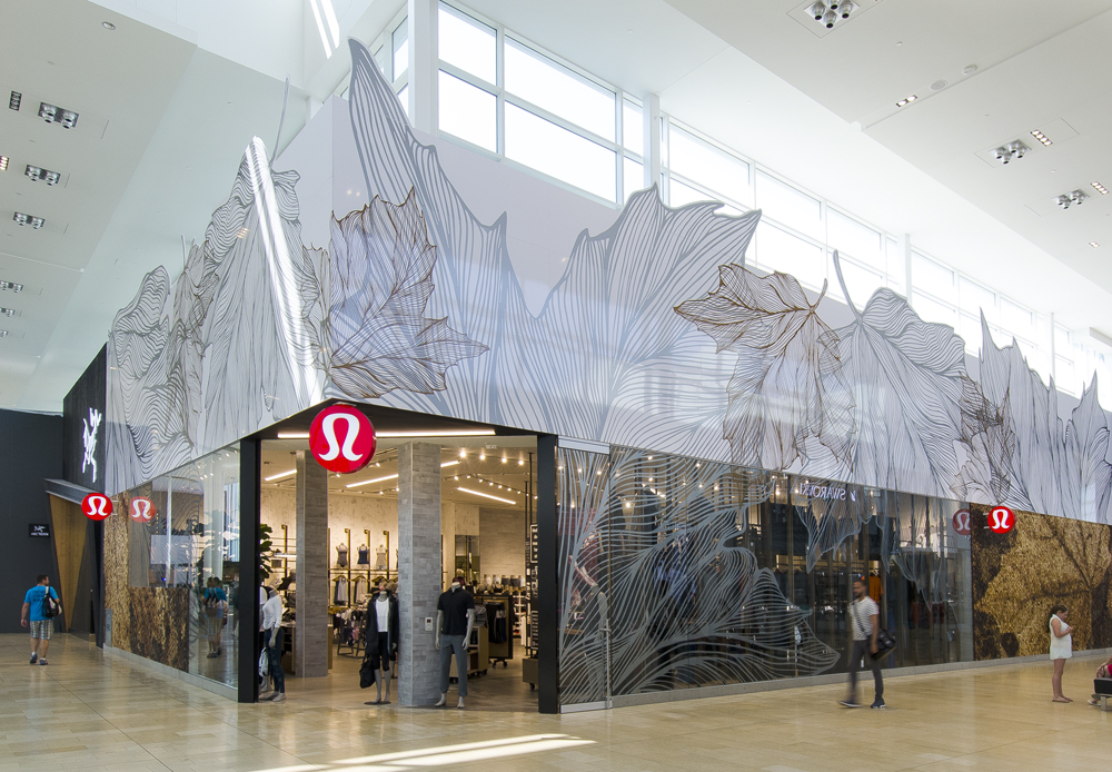 a mall storefront corner unit for Lululemon, made of glass with large white maple leaf decals
