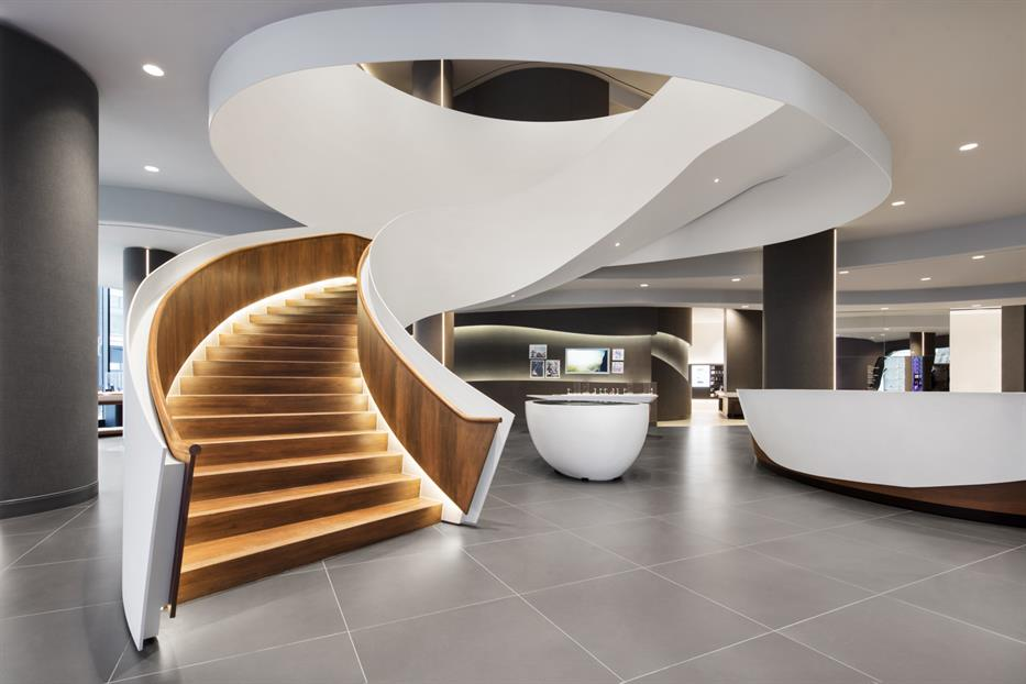 a grand curving staircase with wooden steps and handrails, framed in white steel