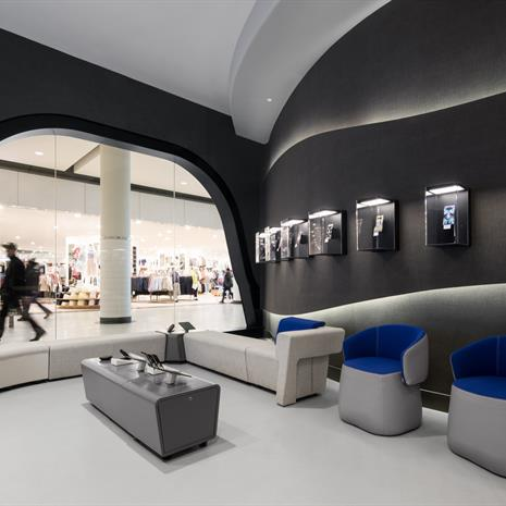 the seating area of the personalization zone at the Samsung Experience Store, one-of-a-kind phone cases in displays on the wall and a window with rounded edges shows the Eaton Centre hallway