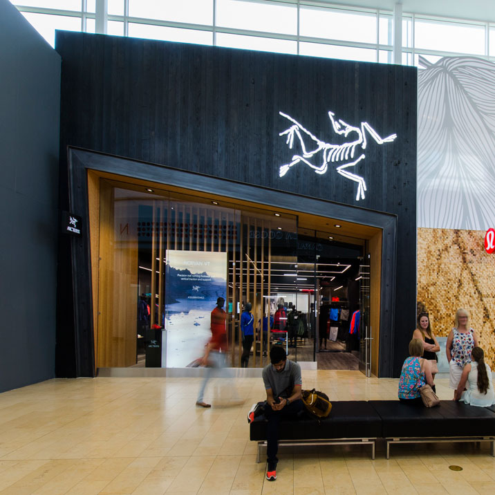 mall storefront of Arc'teryx, made of black wood with a dinosaur fossil shaped LED above the angled entryway