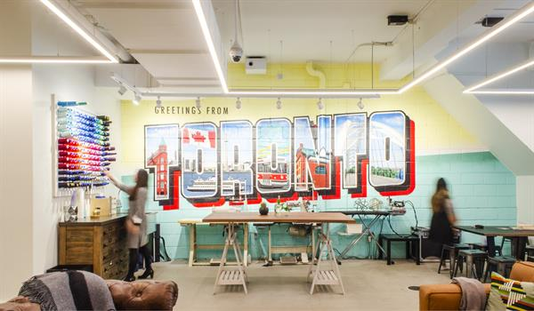 """Colourful mural of the words """"Greetings From Toronto"""", spools of thread affixed to the wall, and leather couches in the foreground"""