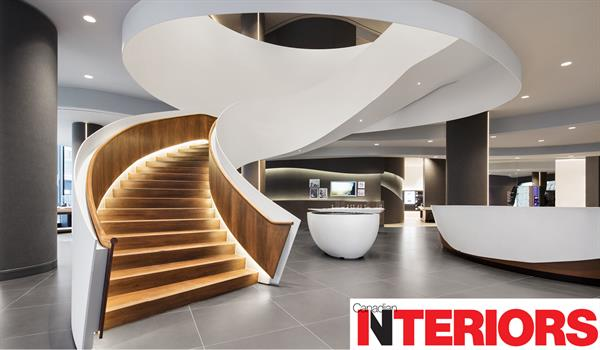 a grand curving staircase encased in white steel with downlighting on the warm wooden steps and the Canadian Interiors logo in the bottom right corner
