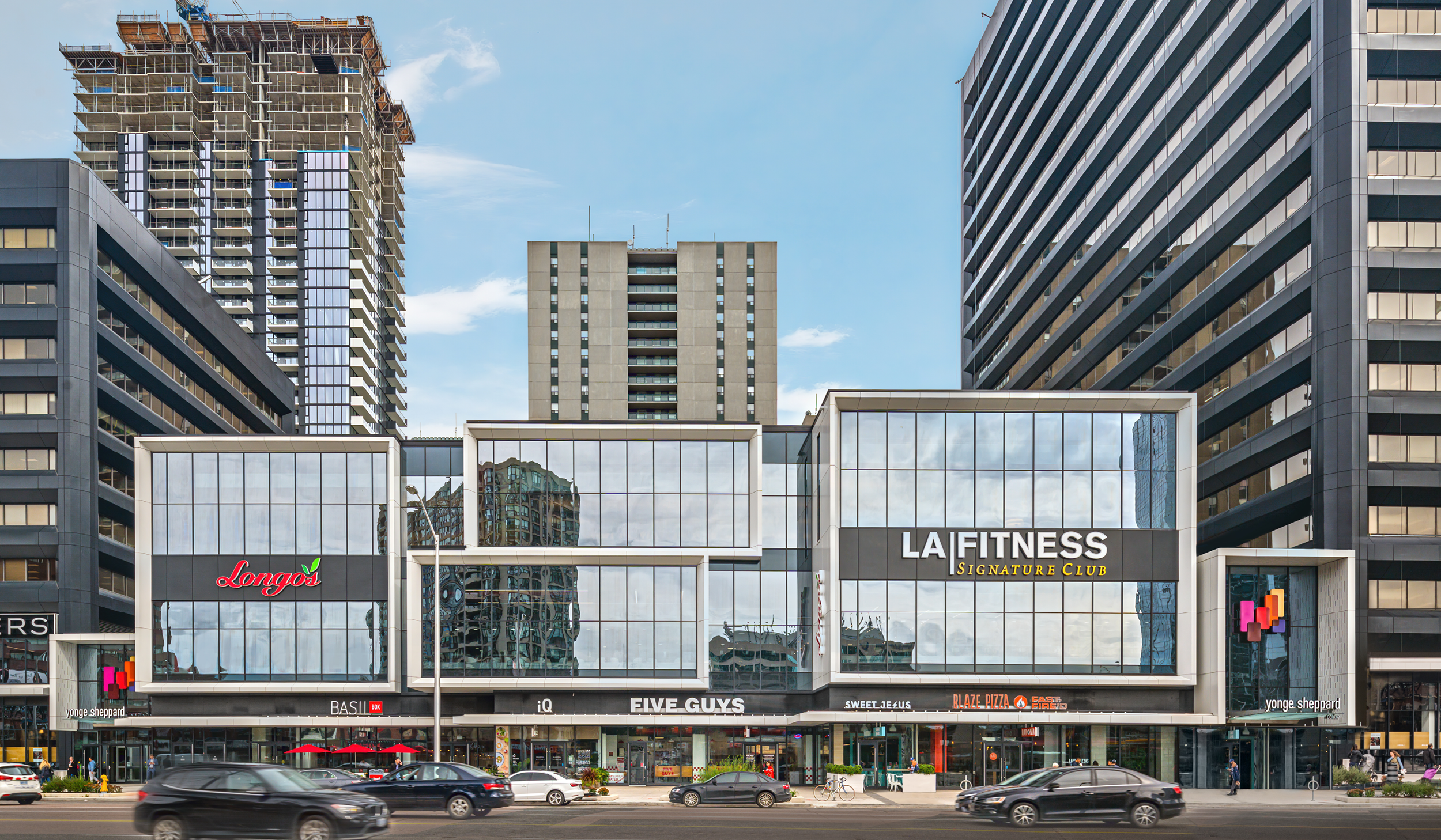 entrance to Yonge Sheppard Centre with new modern white framing and large glazed expanses, connected in between to black clad office towers, with a high rise residential tower under construction in the background