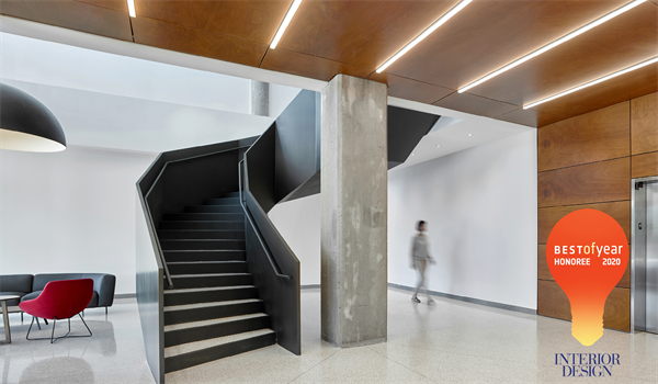 lobby of Bata Shoe Factory apartment building showing black matte metal curving feature stair and wooden ceiling feature and wood framed elevator bay, with the orange lightbulb logo of the Interior Design Best of Year Awards Honouree 2020 designation