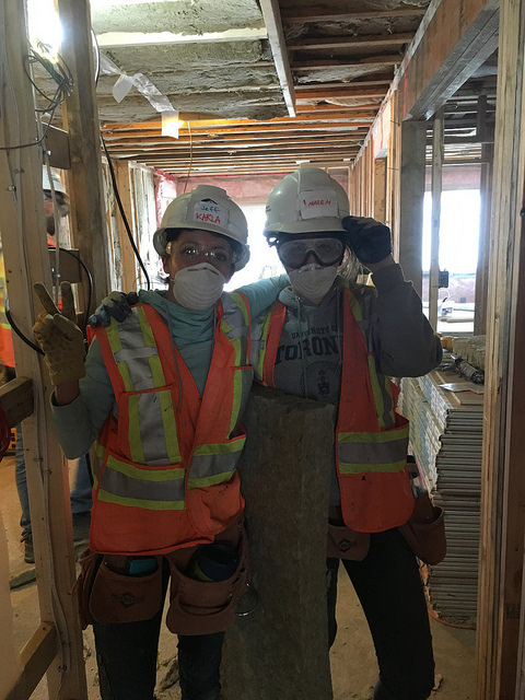 two women wearing hard hats and safety vests with their arms around each other's shoulders on a construction site