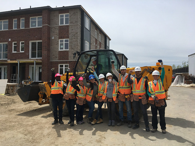 9 people in hard hats and safety vests raise their fists while standing in front of a backhoe