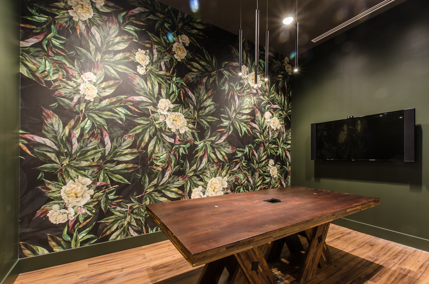 a meeting room with forest green walls and a floral accent wall, wooden floors and wooden conference table