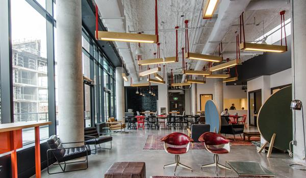 Interior of the Commons lounge area in Artscape Daniels Launchpad showing wooden light fixtures hanging from red cords, leather seating and wine coloured rugs