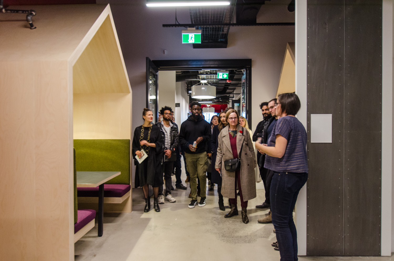 Tor McGlade leading an interior design tour at Artscape Daniels Launchpad, showing the group a covered wooden seating nook with olive and plum cushions