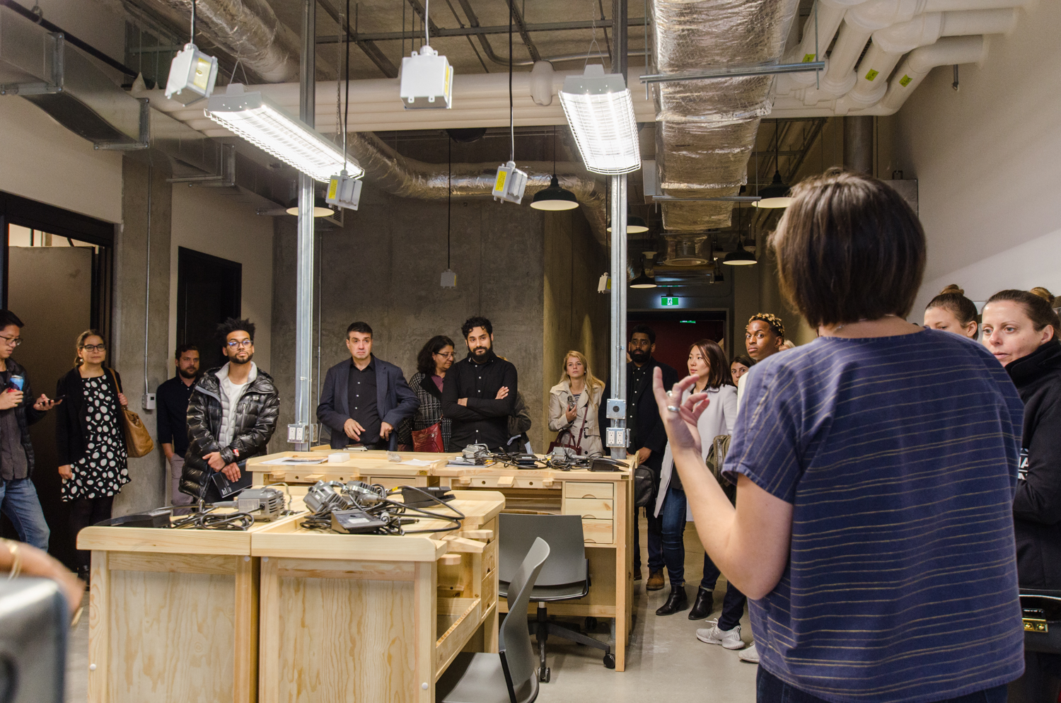 Tor McGlade leading an interior design tour of Artscape Daniels Launchpad, showing the group a prototyping workshop with wooden work stations