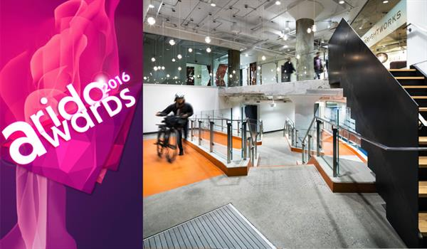 photo of someone walking their bike up a bright orange ramp inside the 100 Broadview lobby, with the ARIDO Awards 2016 logo to the right