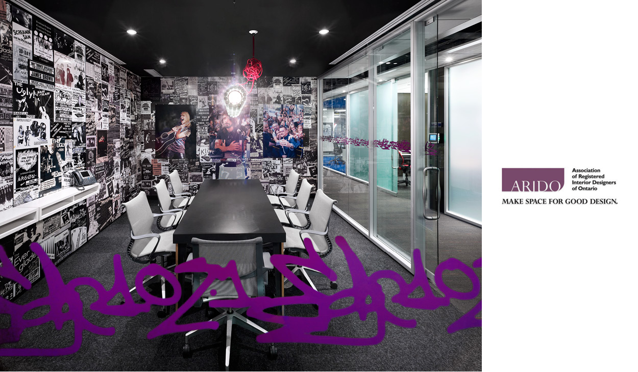 a boardroom with purple graffiti on the glass wall and a wallpaper collage of classic rock bands