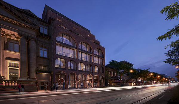 rendering of a midrise condo in an urban high street setting, with red brick facade that has arches framing the large windows