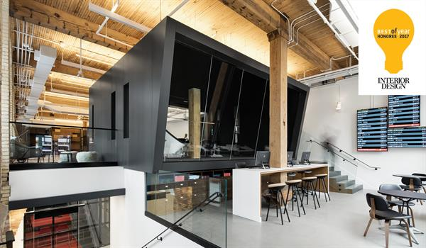 a black framed, angular boardroom in a brick and beam building with exposed walls and ceiling