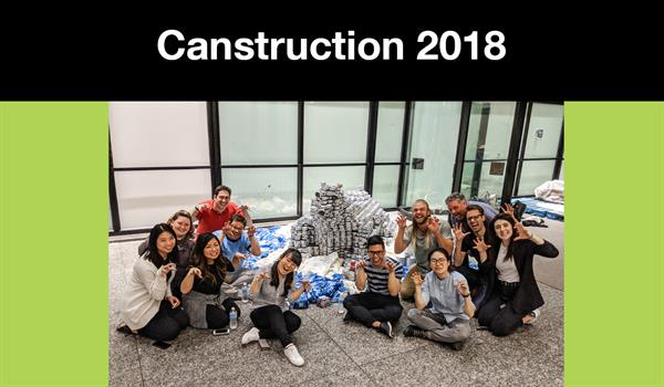 a group of Quadrangle staff seated around a polar bear structure made out of canned foods with the heading Canstruction 2018