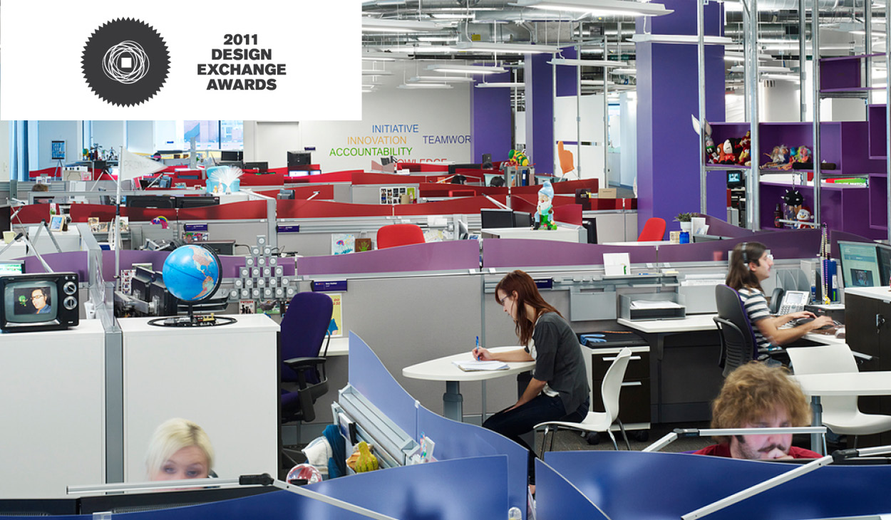 people work at desks with colourful partitions in an open office environment
