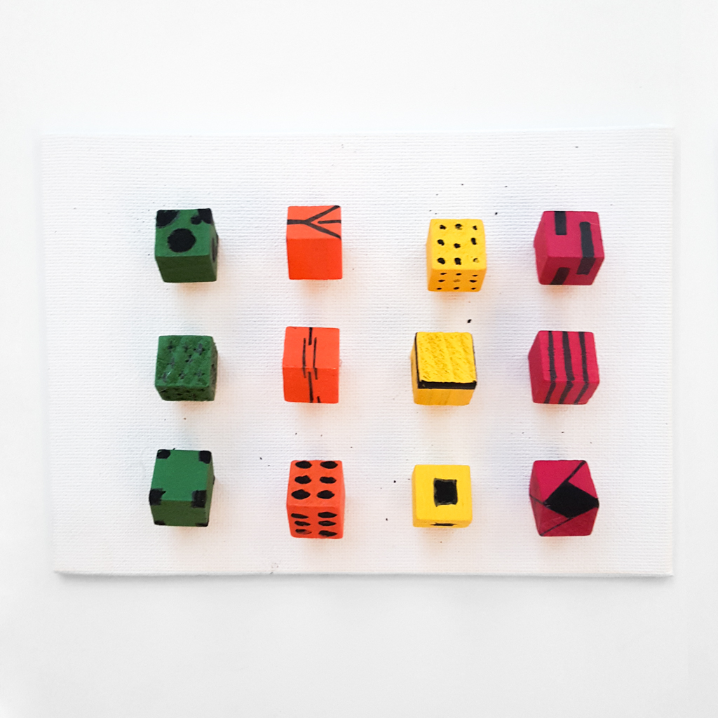 green, orange, yellow, and red cubes with different patterns protrude from white canvas