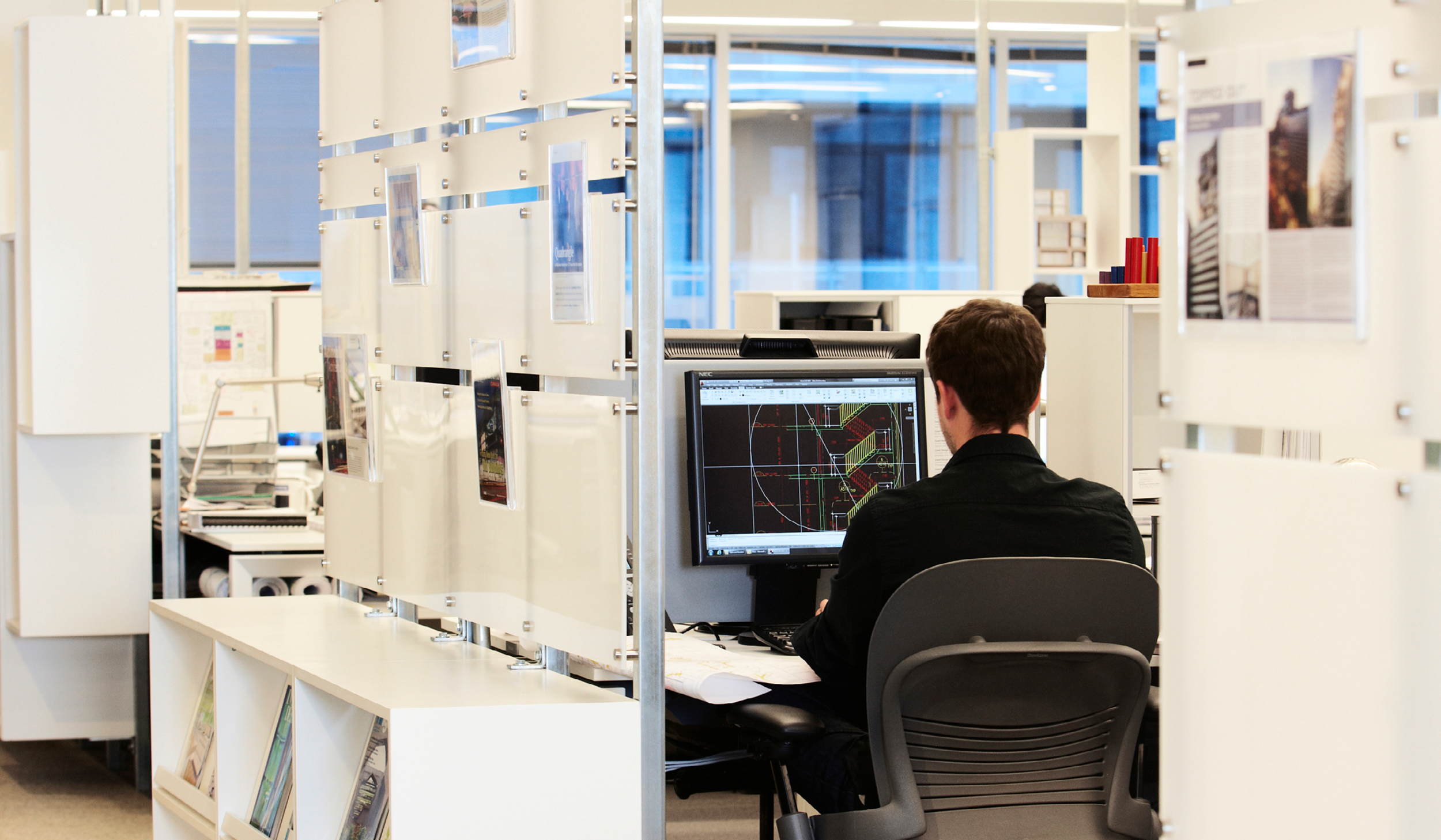 an architect sitting at his workstation working on Revit on his computer