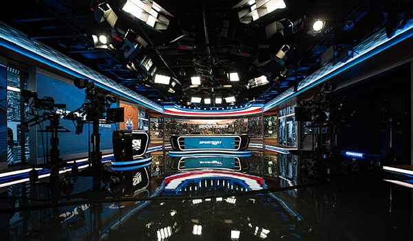 broadcast studio for a sports tv network with desks, sets and professional lighting