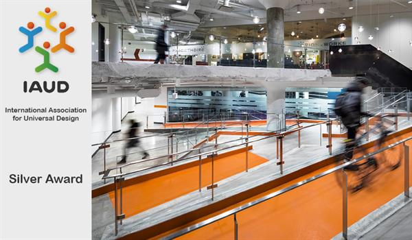 a person walks their bike up a bright orange ramp in the 100 Broadview lobby