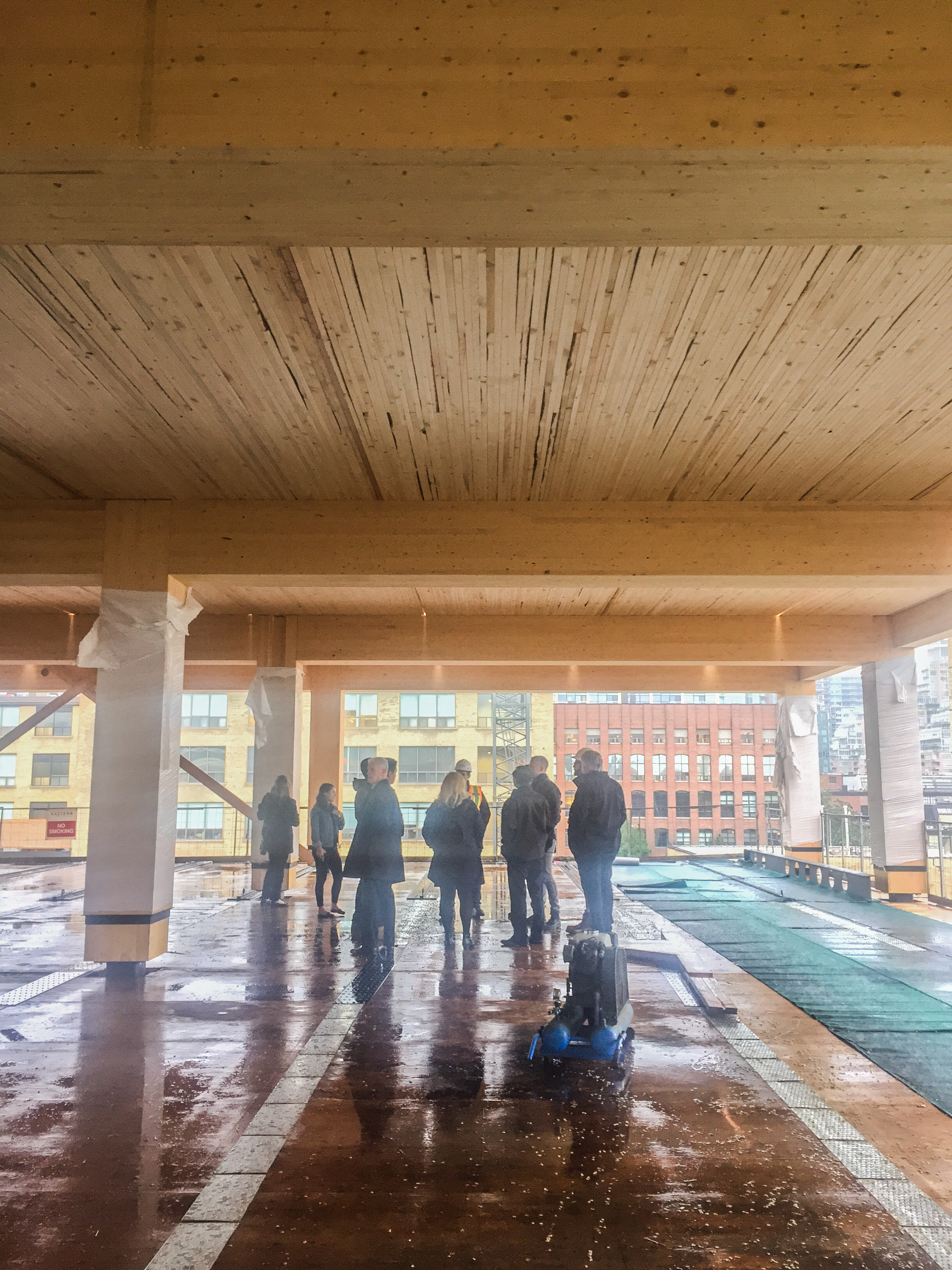 a group of people standing in the under construction 80 Atlantic lookign at the wood post and beams and NLT deck timber ceiling