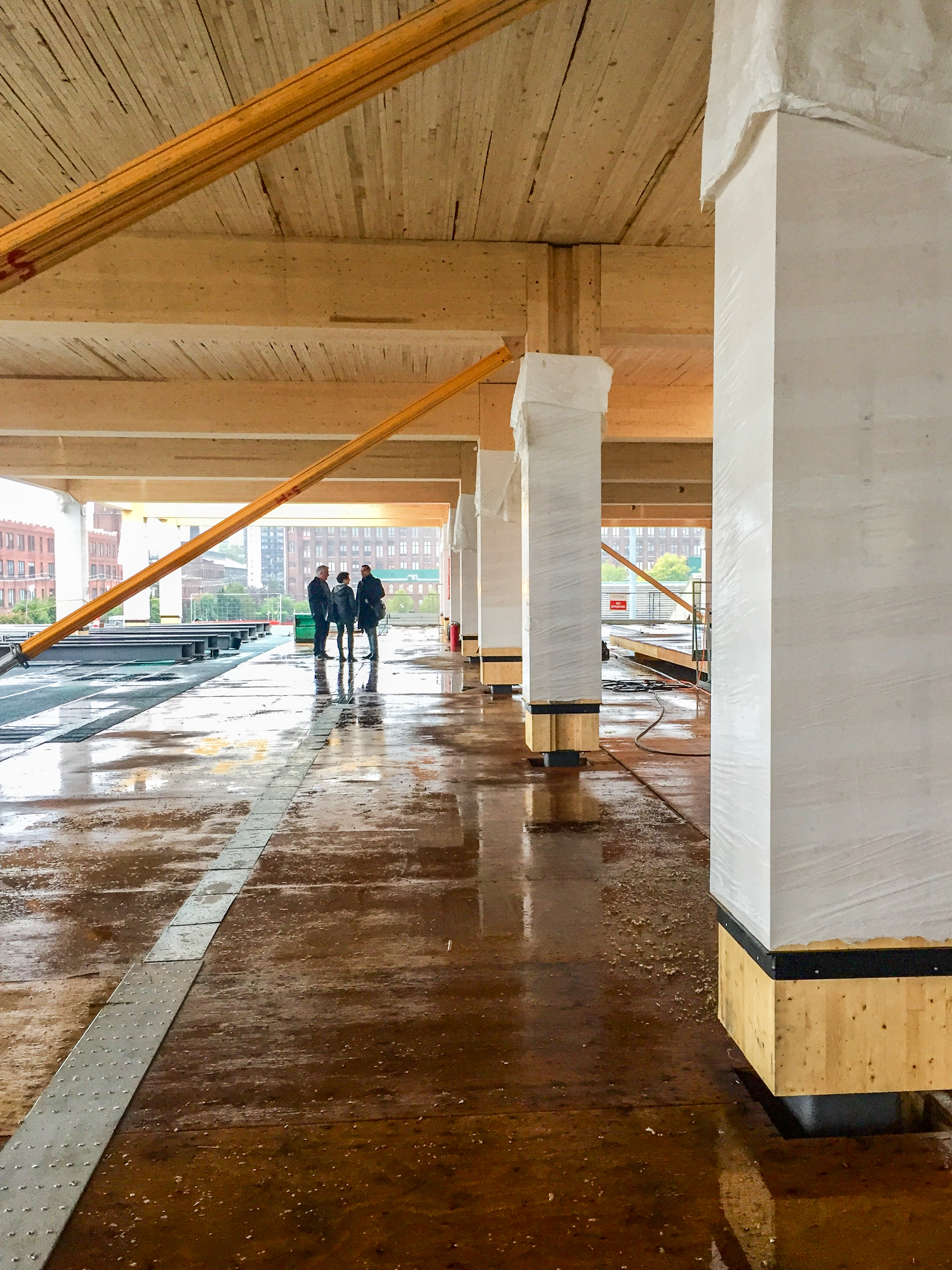 three people in the distance standing in the under construction 80 Atlantic lookign at the wood post and beams and NLT deck timber ceiling, temporary braces are installed at the post and beams