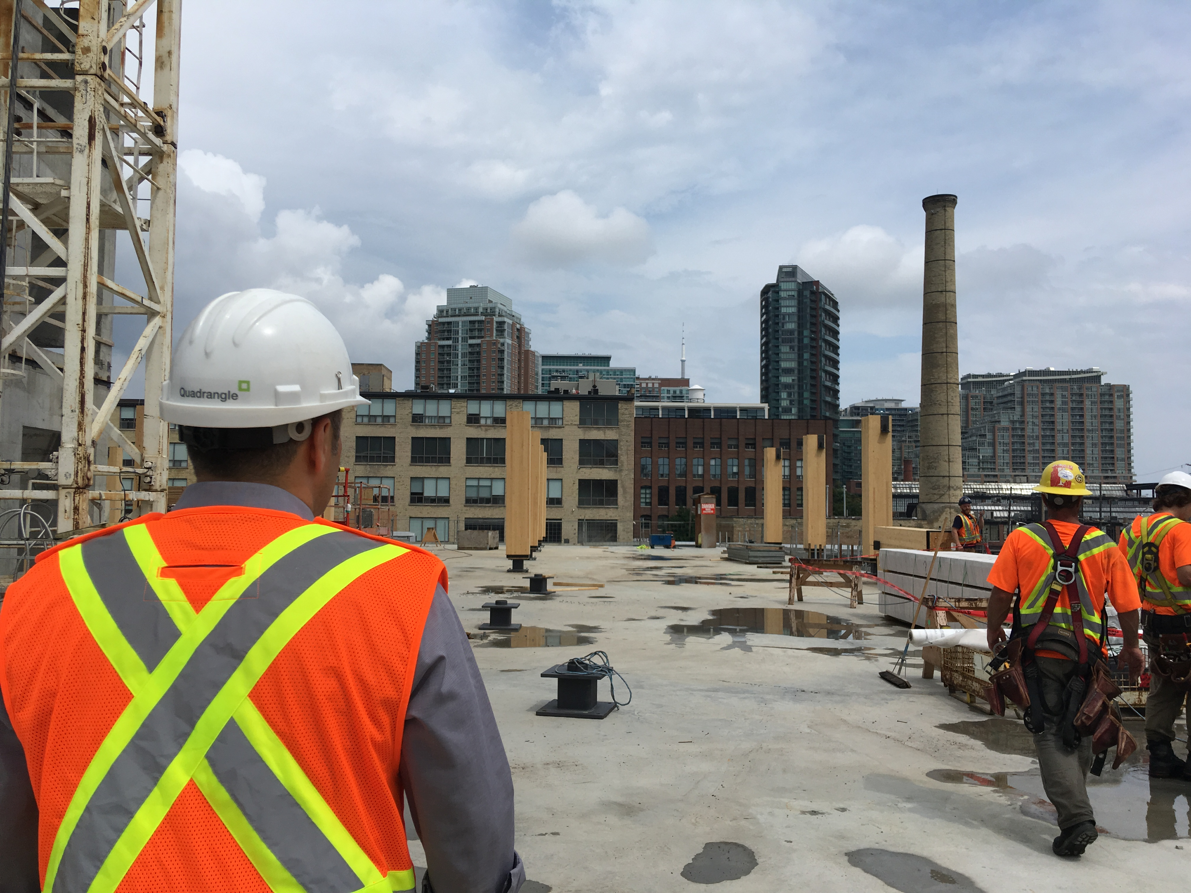 Richard Witt seen from behind wearing safety vest and Quadrangle branded hard hat in teh foreground on site at 80 Atlantic looking at upright glulam columns and Liberty Village condos and heritage smokestack in the distance