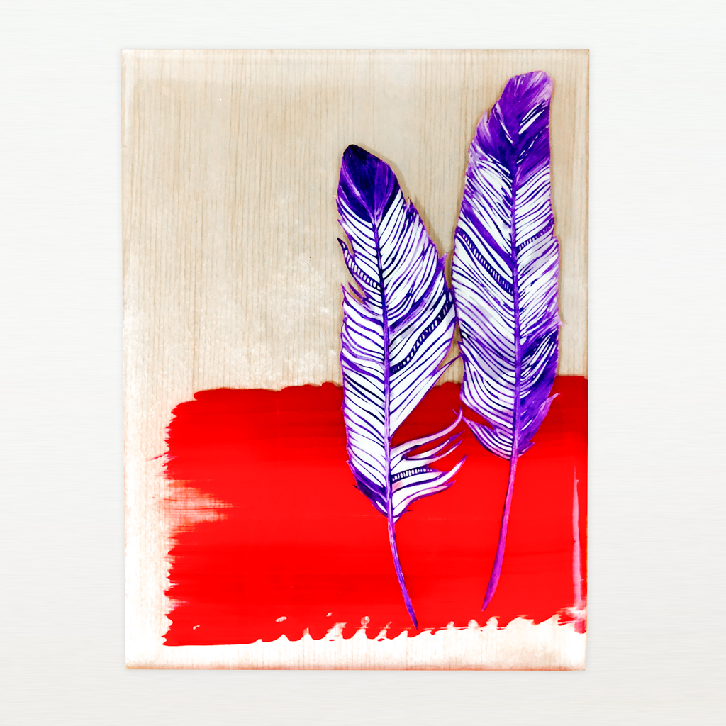purple feathers and red swath of paint floating in resin on a wood panel