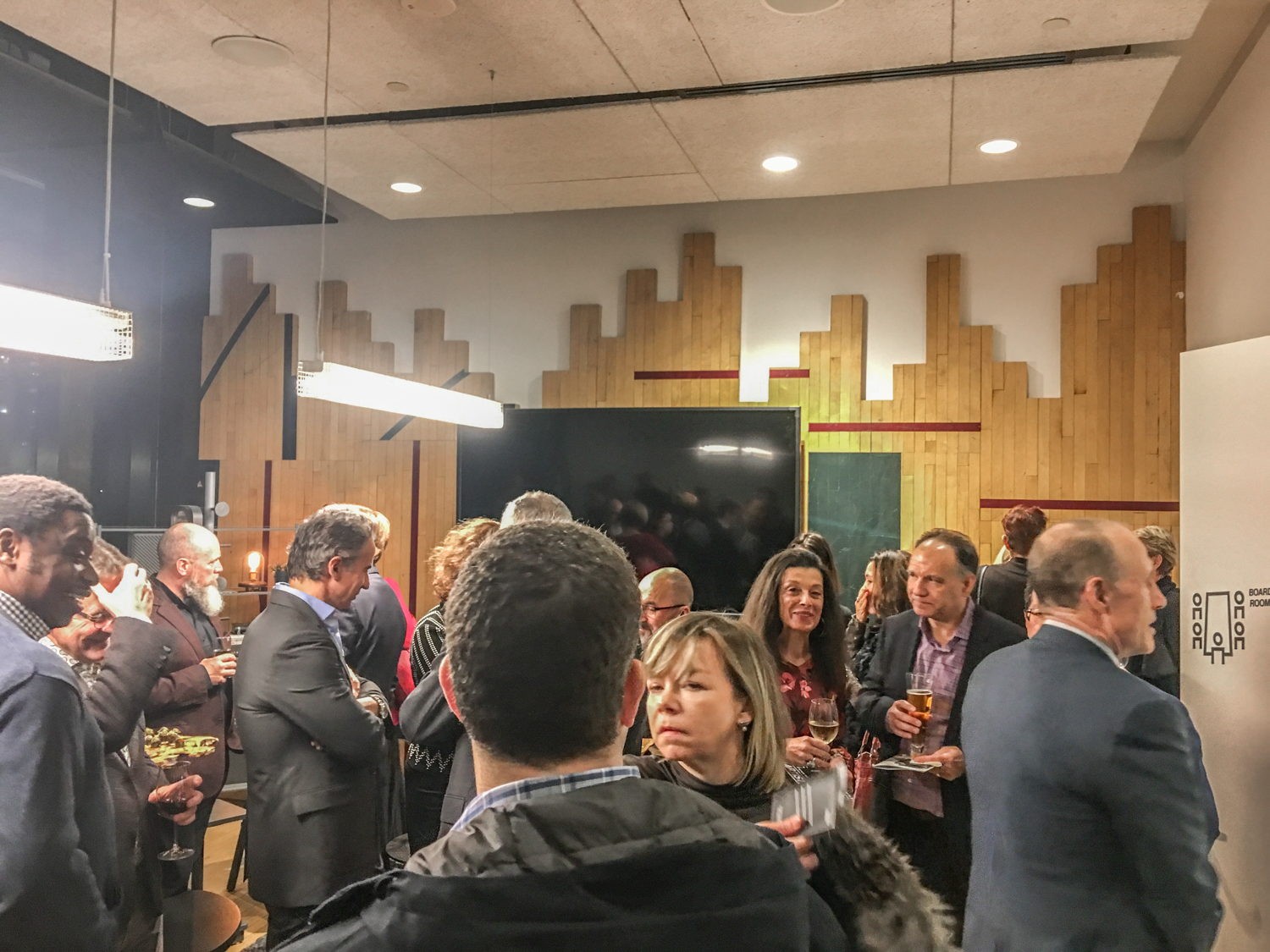 a crowd mingles in a boardroom that has repurposed gym flooring used as a wallcovering