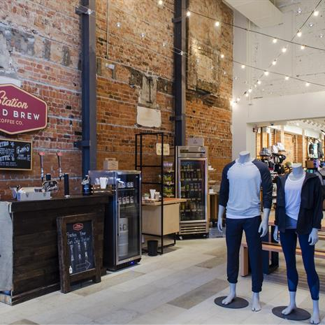 Inside of a store with a coffee and juice bar against an exposed brick will, hanging string lights, and mannequins in athleisure wear in the foreground