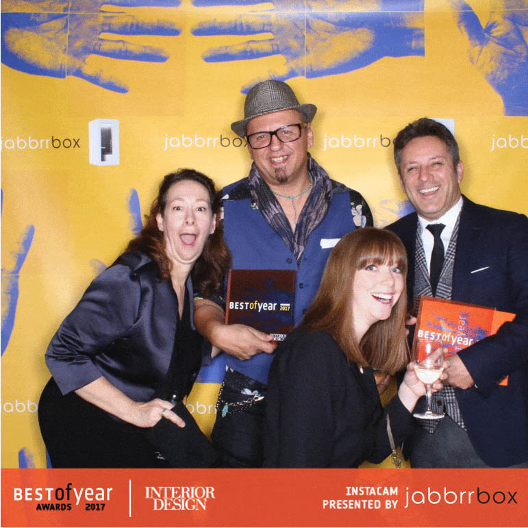 Caroline, Richard, George, and Andrea posing in front of an Interior Design branded wall holding their finalists plaques