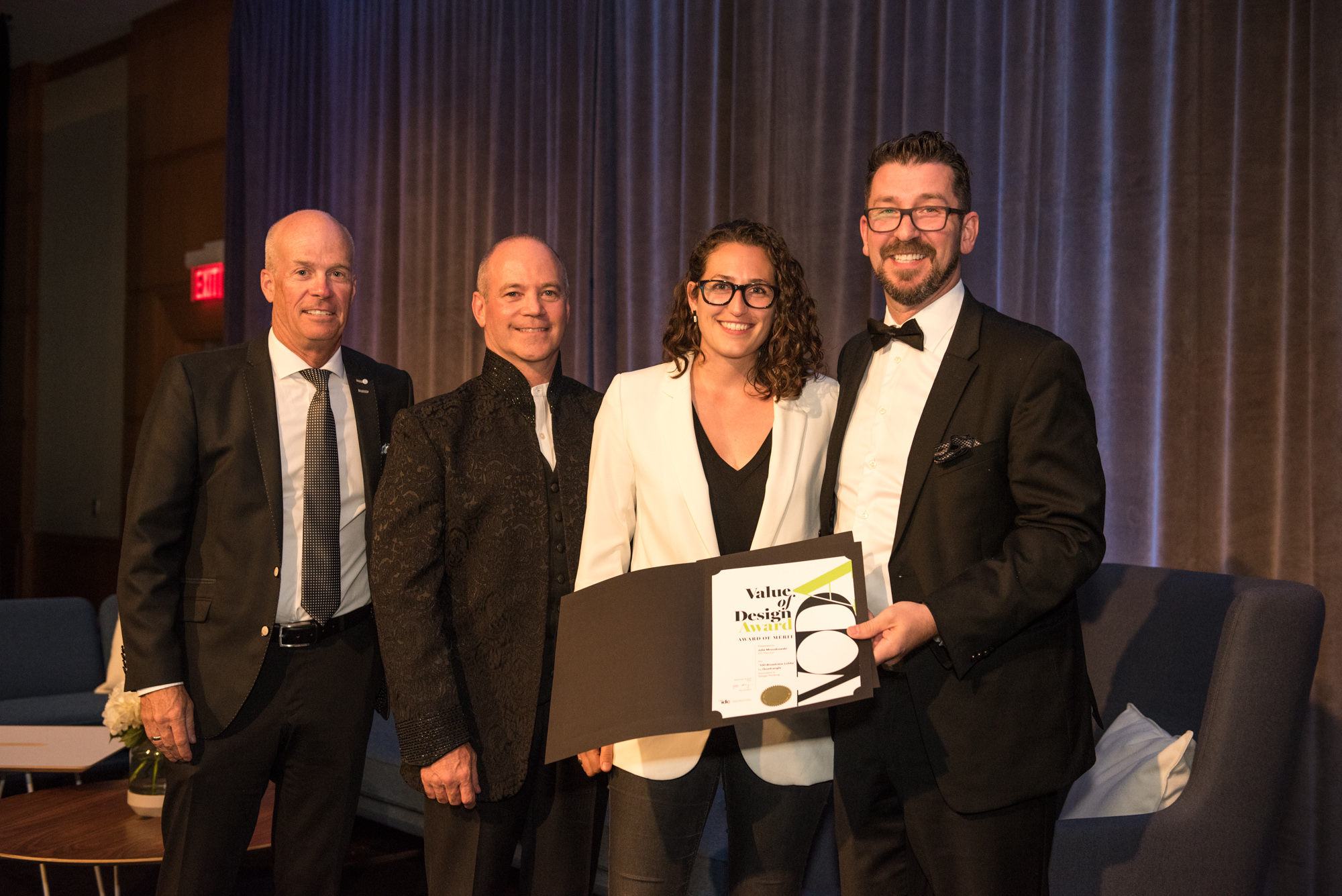 Quadrangle Associate Julie Mroczkowski posing for a photo with three men in suits, accepting a Value of Design Awards certificate