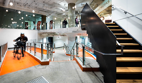 a person walks a bike up a bright orange ramp in a commercial building lobby with raw concrete floors and a black steel encased staricase with wooden steps
