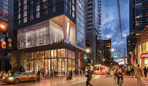 A bustling King Street at dusk showing the podium of 357 King with its glazed box base framed in black, and the glazed indoor/outdoor amenity between the podium and condo tower. two angled white columns on the amenity terrace support the upper tower.