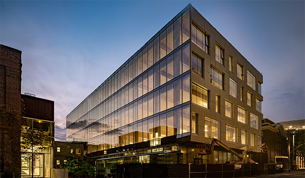 office building at dusk with a glazed south wall showing exposed wood ceilings and columns