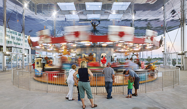 families watch a colourful carousel as it spins