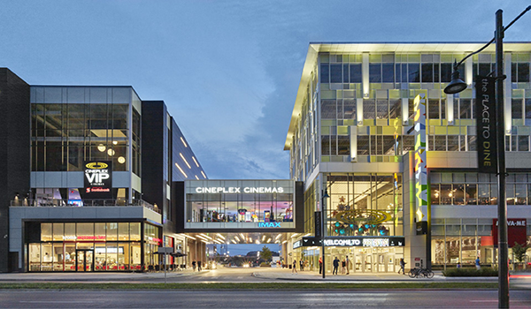 two midrise retail and office mixd-use buildings lit up at dusk, connected with an elevated pedestrian walkway over a road