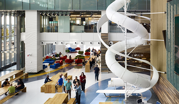 lobby of Corus Entertainment with long wooden benches, lounge seating in primary colours and a white spiral slide