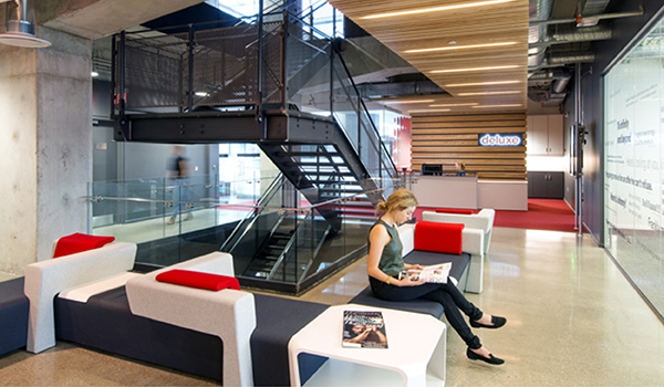 office reception with wooden panels on ceiling and behind reception desk, a woman sits on lounge furniture with bright red pillows