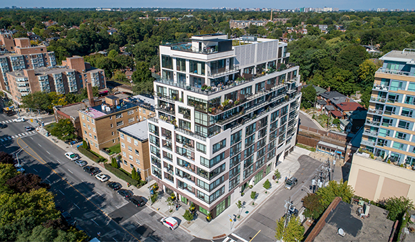 aerial photo of a mid-rise condominium with white cladding and inset balconies
