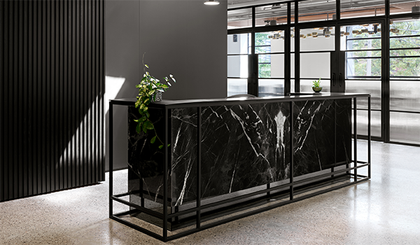 a dark green marble reception desk with matte black wall behind it and a hall of closed meeting rooms separated by factory-style steel screens