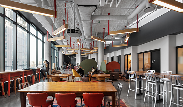 The common area in Launchpad showing a range of table and chair types and wooden light fixtures hanging from red cords