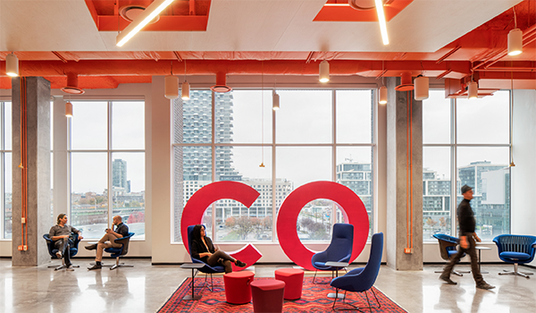 3 people sit in lounge seating and one person walks in OCAD U CO's common area with a bright orange ceiling and pink 6 foot tall C O letters in front of floor-to-ceiling windows