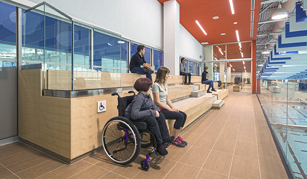 people of varying abilities using accessible wooden bleachers in a viewing gallery looking over a pool