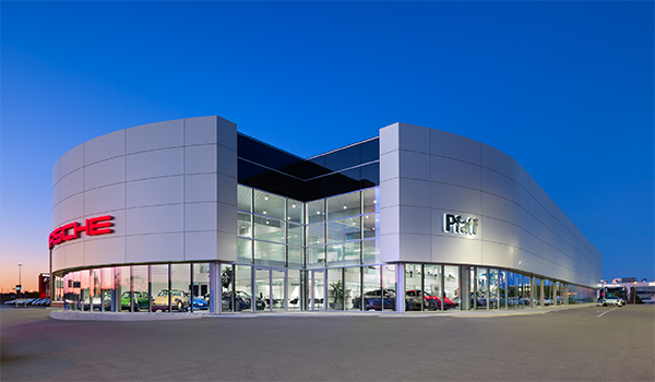 round, grey-clad Porsche dealership building with glazing at grade and a glazed cut out corner at the entrance