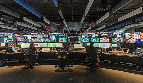 a man and a woman seated in front of a wall of computer monitors showing different media being broadcast