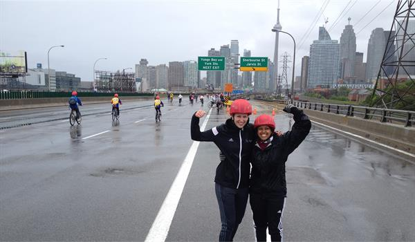 two women wearing bicycle helmets raise their fists in the air while standing on the Gardiner Expressway during Ride For Heart 2015