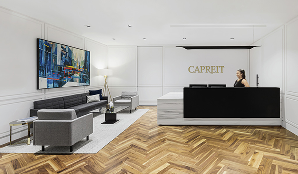 lobby of the CAPREIT Offices with a white marble reception desk, wooden floors and grey furniture
