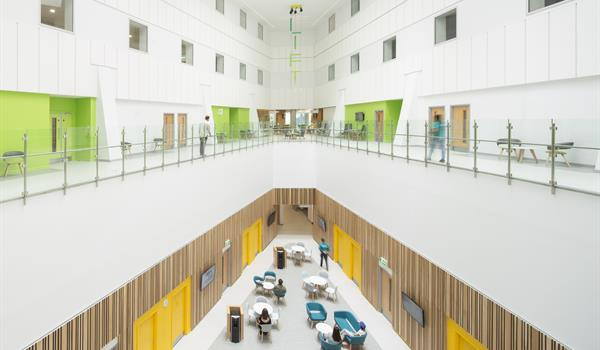 overlooking an atrium inside the Clatterbridge Cancer Centre which has wooden walls and yellow doorways on the lower level and crisp white walls and lime green doorways on the second level with skylights overhead